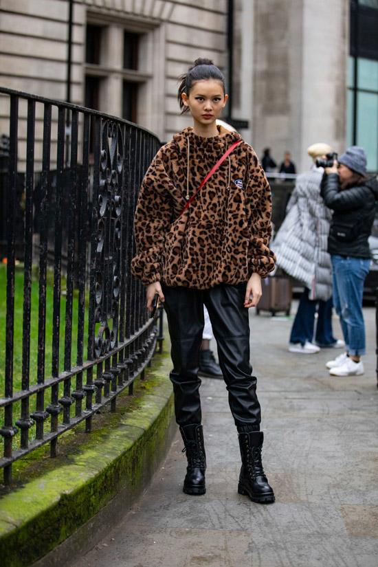 Девушка в кожаных брюках, полушубок с леопардовым принтом и черные грубые ботинки