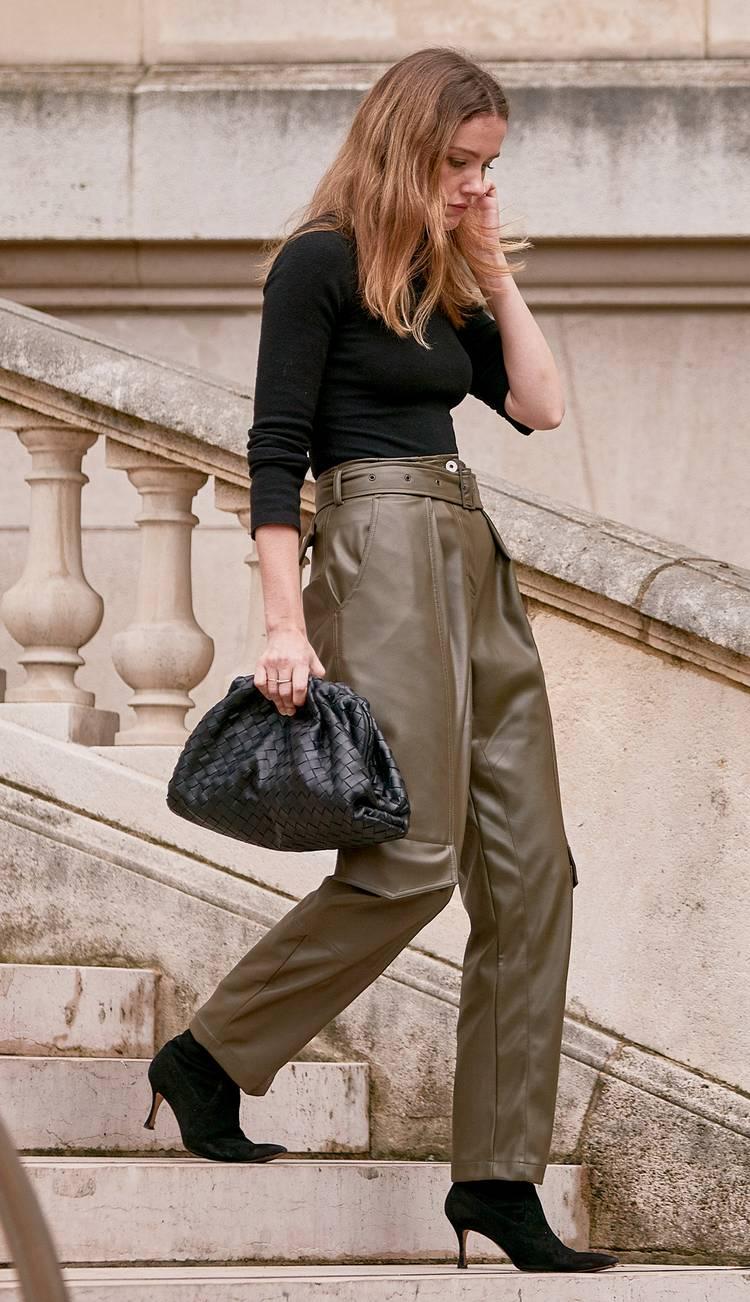 Девушка в кожаных брюках цвета хаки, черная водолазка, ботильоны и мягкая сумочка