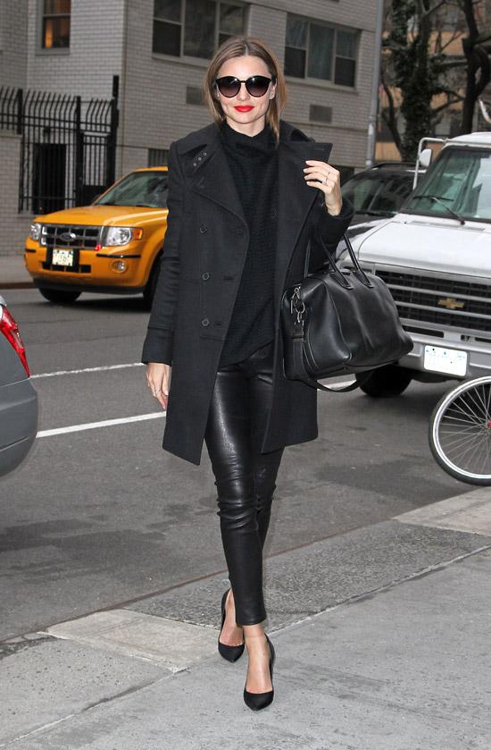Девушка в кожаных леггинсах, черное пальто и большая сумка