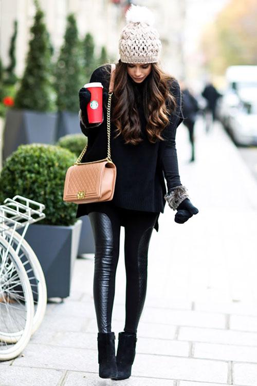 Девушка в кожаных леггинсах, черный джемпер оверсайз, ботильоны и вязаная шапка