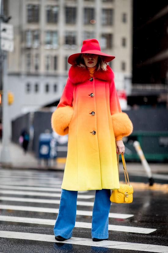 Девушка в красно-желтом пальто омбре, синие джинсы и красная шляпа