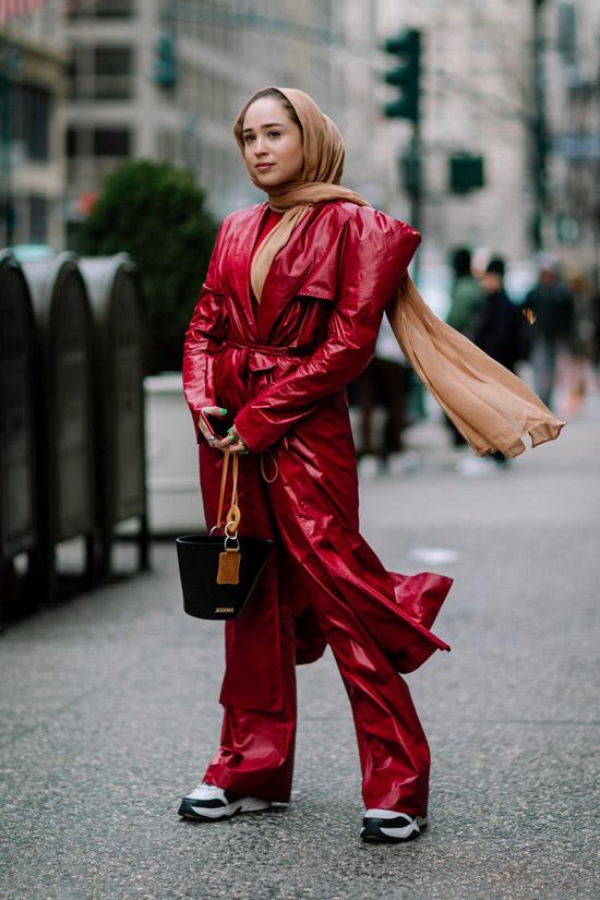Девушка в красных брюках, яркий плащ с поясом и бежевый шарф