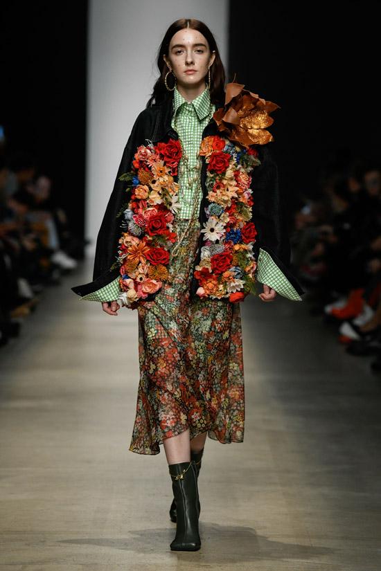 Девушка в легкой миди юбке, черные ботильоны и куртка с цветочным принтом