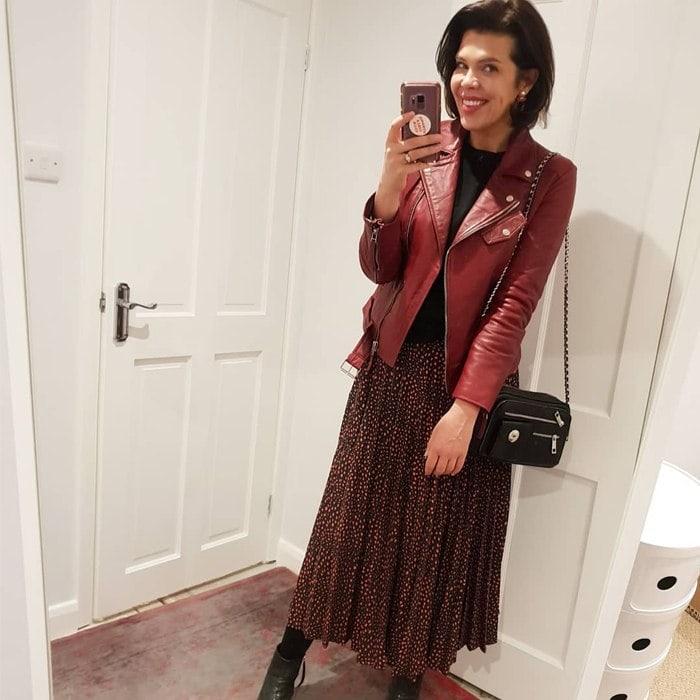 Девушка в легкой юбке миди, красная кожаная куртка и сумка