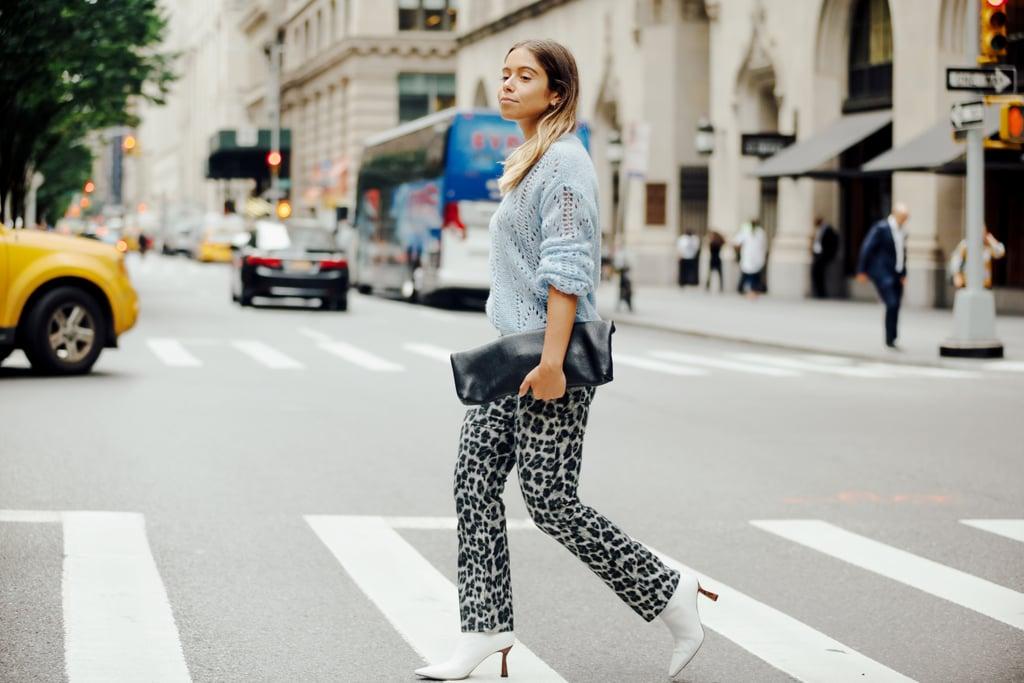 Девушка в леопардовых брюках, голубой свитер и белые ботильоны
