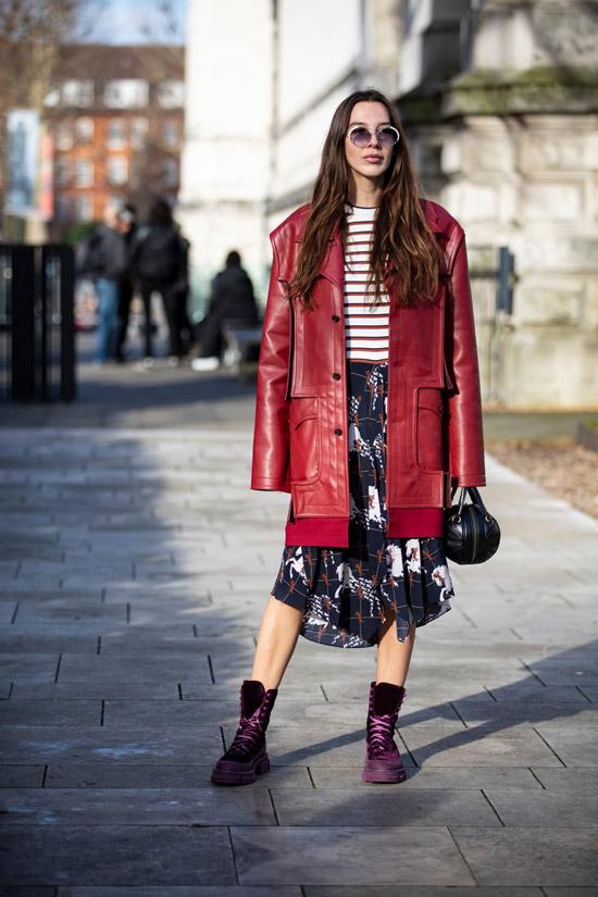 Девушка в миди юбке, красный кожаный плащ и грубые ботинки на шнуровке