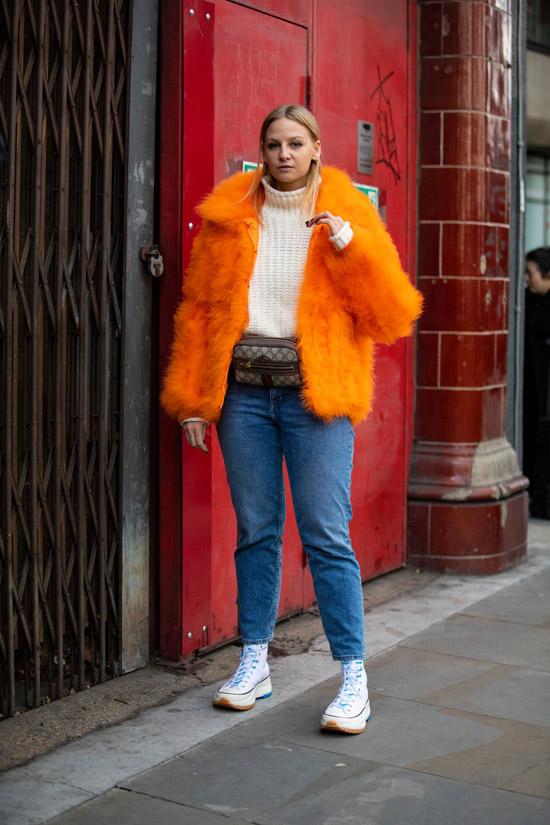 Девушка в оранжевой короткой шубе, синие джинсы и поясная сумка