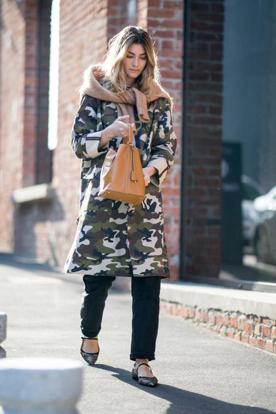 Девушка в плаще цвета хаки, черные брюки и бежевый свитер
