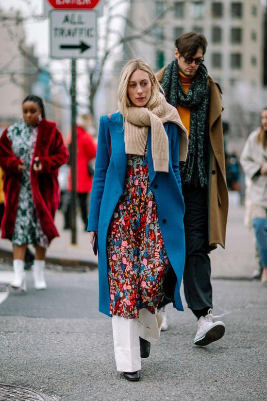 Девушка в платье миди с цветочным принтом, синее пальто и бежевый свитер на шее