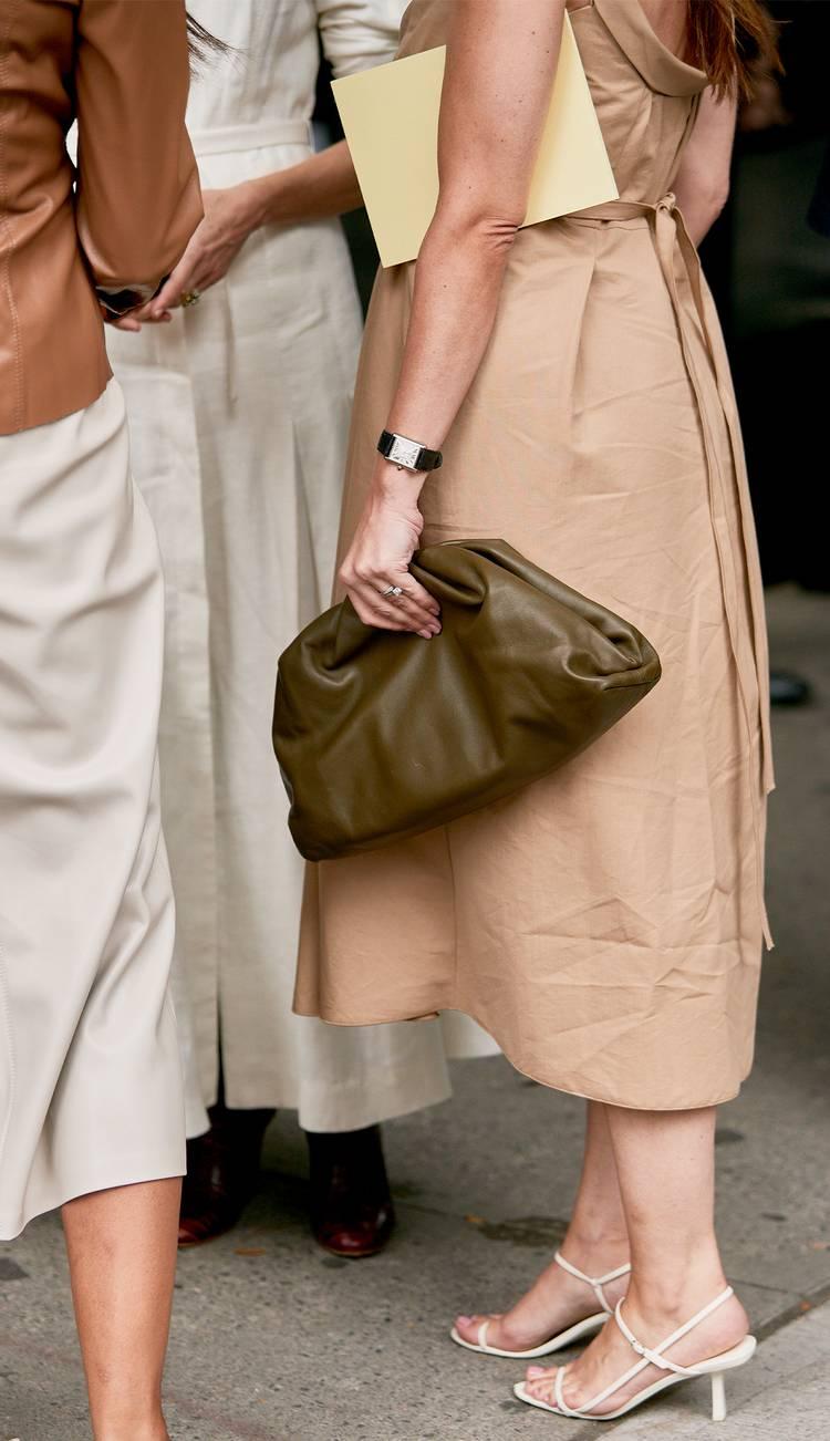Девушка в простом бежевом платье, белые босоножки на ремешках и зеленый мягкий клатч