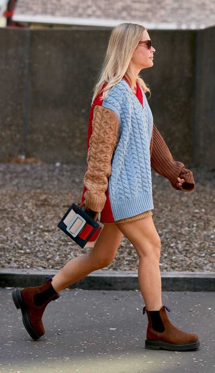 Девушка в разноцветном вязанном свитере, коричневые ботинки на плоской подошве и маленькая сумочка с пряжкой