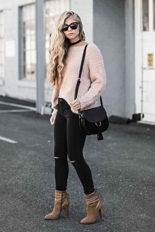 Девушка в рваных черных джинсах, розовый свитшот и ботильоны на каблуках