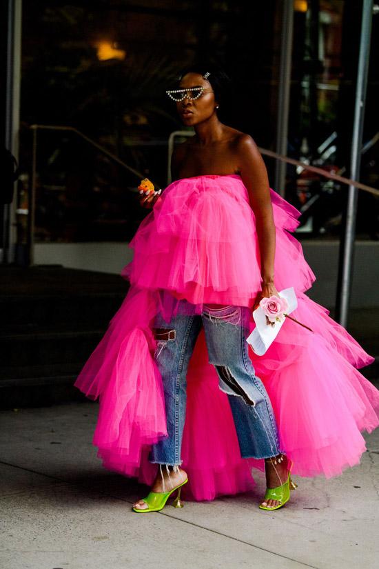 Девушка в рваных джинсах и розовый асимметричный топ из тюля