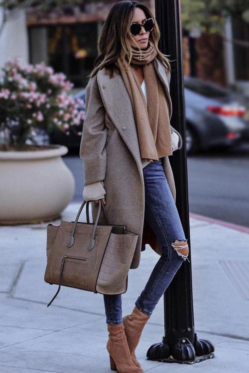 Девушка в рваных синих джинсах, уютное пальто и объемная сумка