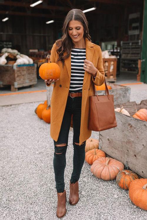 Девушка в рваных узких джинсах, футболка в полоску, оранжевое пальто и коричневые ботильоны