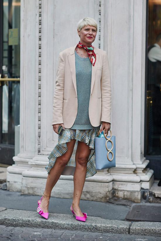 Девушка в сером джемпере, асимметричная юбка, розовый блейзер и шелковый платок на шее