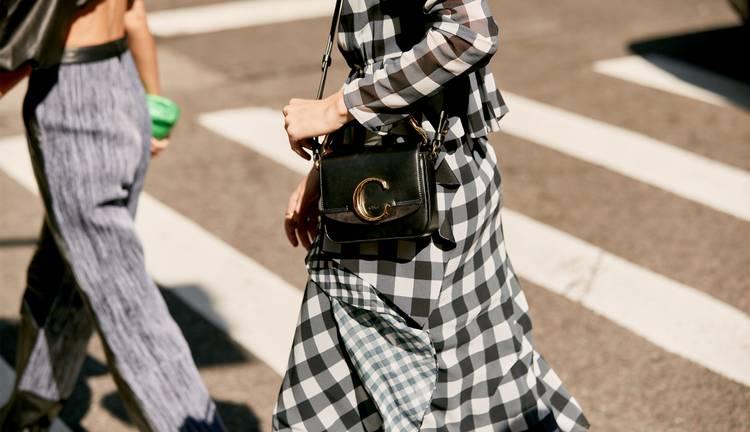 Девушка в сером костюме в клетку, черная сумочка