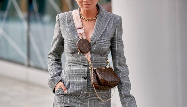 Девушка в сером жакете в клетку и коричневая сумочка