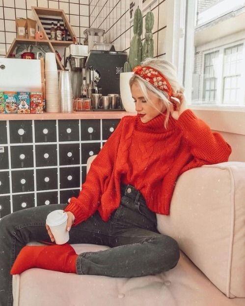 Девушка в серых джинсах, красный свитер и ботильоны на шпильке и бархатный ободок