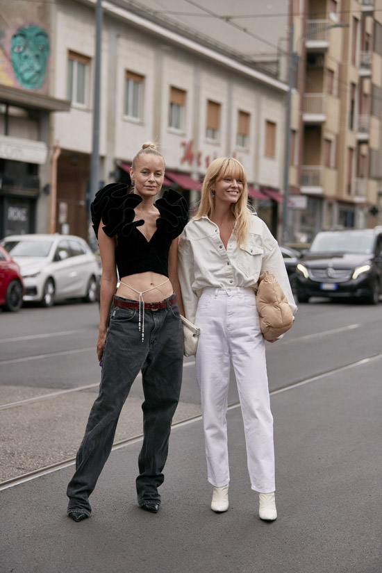 Девушка в серых джинсах с ремнем, черный топ с пышными плечами