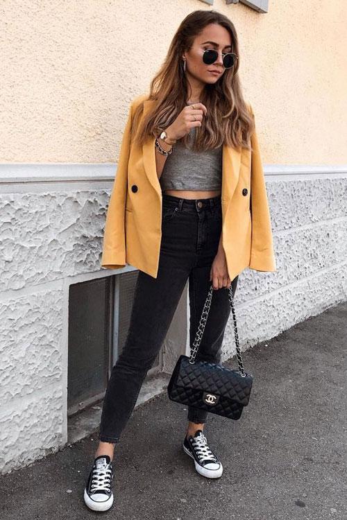 Девушка в серых джинсах с завышенной талией, кроп топ и желтый блейзер