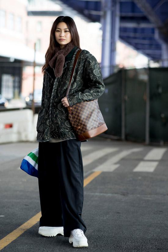 Девушка в широких брюках, куртка с принтом и белые кроссови