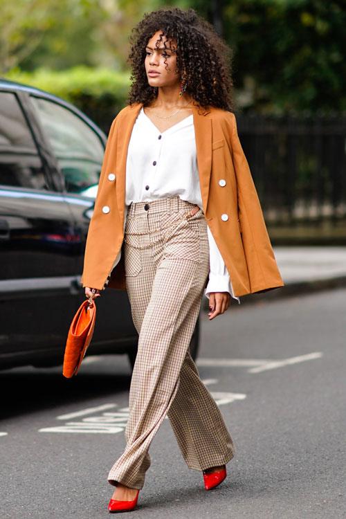 Девушка в широких брюках в клетку, белая блузка и оранжевый блейзер