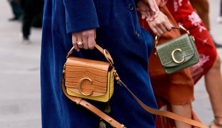 Девушка в синем пальто и маленькая бежевая сумочка