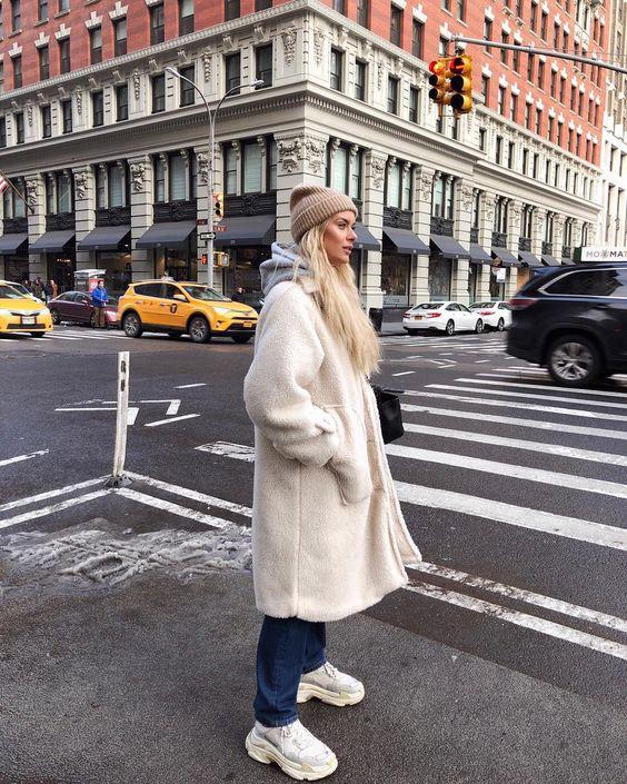 Девушка в синих джинсах, белое меховое пальто и кроссовки