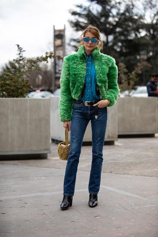 Девушка в синих джинсах с ремнем, зеленая короткая меховая куртка и черные ботильоны