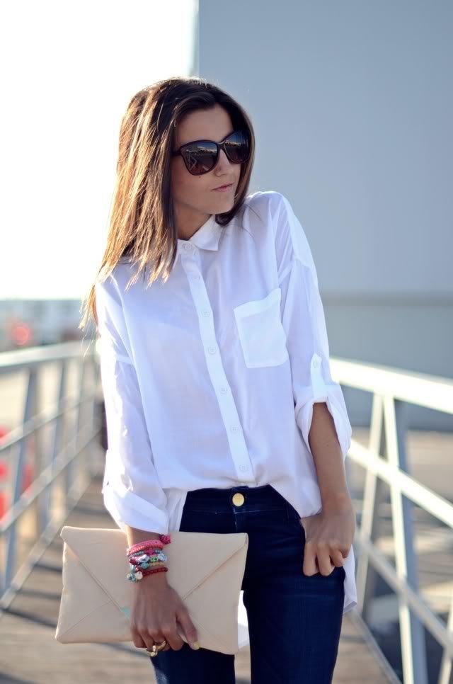 Девушка в синих узких джинсах, белая блузка и бежевый клатч