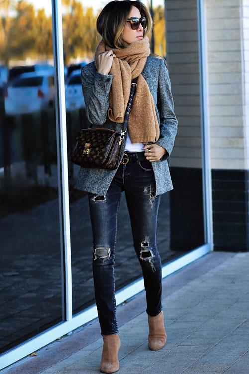 Девушка в синих узких джинсах, серый блейзер и замшевые ботильоны