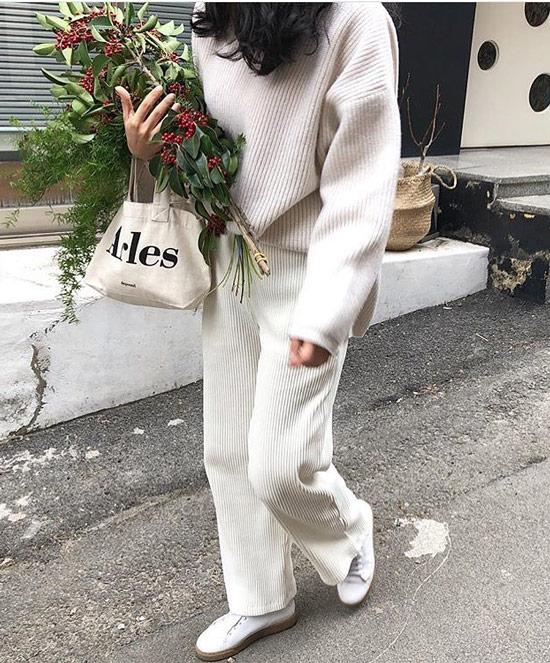 Девушка в светлом трикотажном костюме с брюками и белые кеды