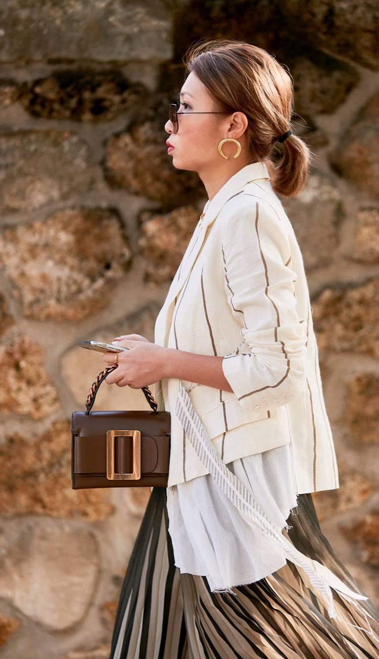 Девушка в светлом жакете, плиссированная юбка и коричневая сумочка с ремешком
