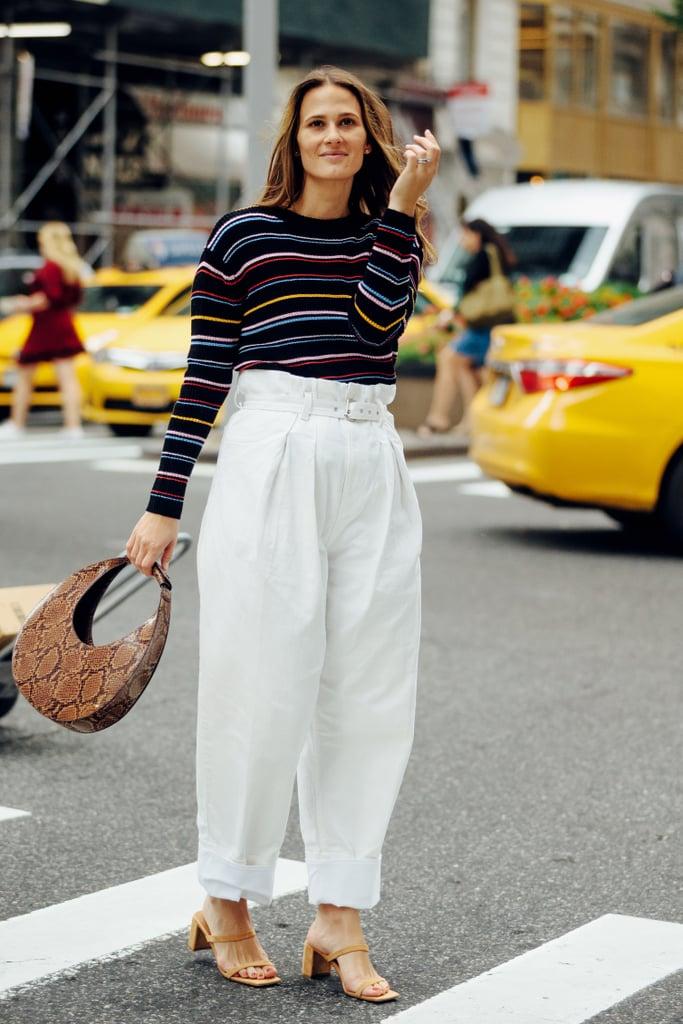 Девушка в свободных белых брюках, свитер с полоску и сумочка из змеинной кожи