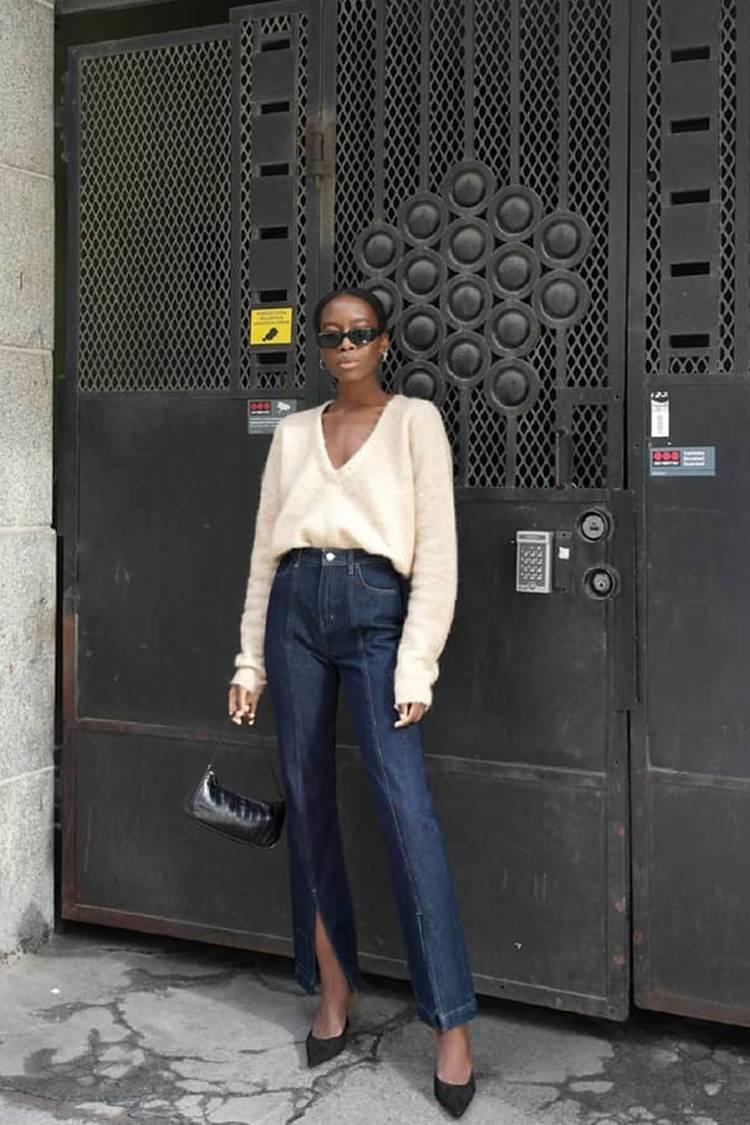 Девушка в темно синих джинсах с завышенной талией, белый джемпер и черные туфли на шпильке