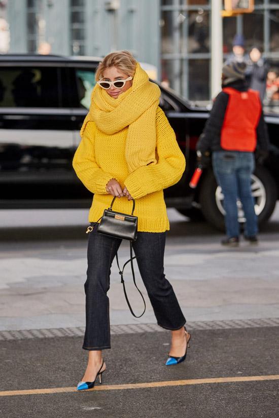 Девушка в темных джинсах, желтый свитер и большой шарф