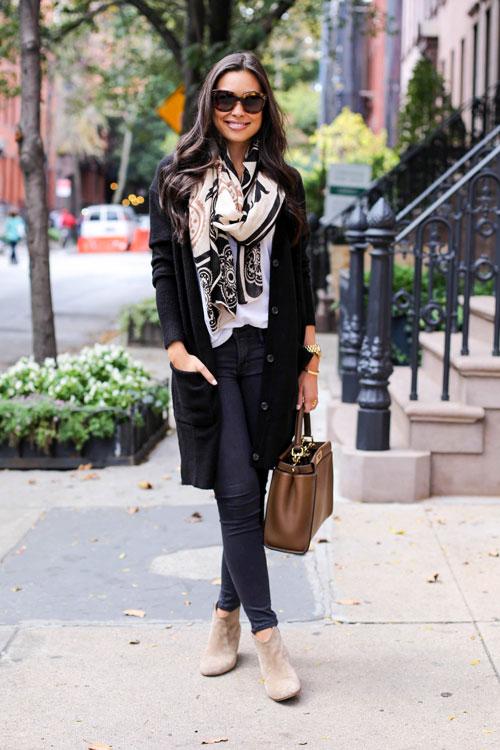 Девушка в темных узких джинсах, черное пальто с палантином и замшевые ботильоны