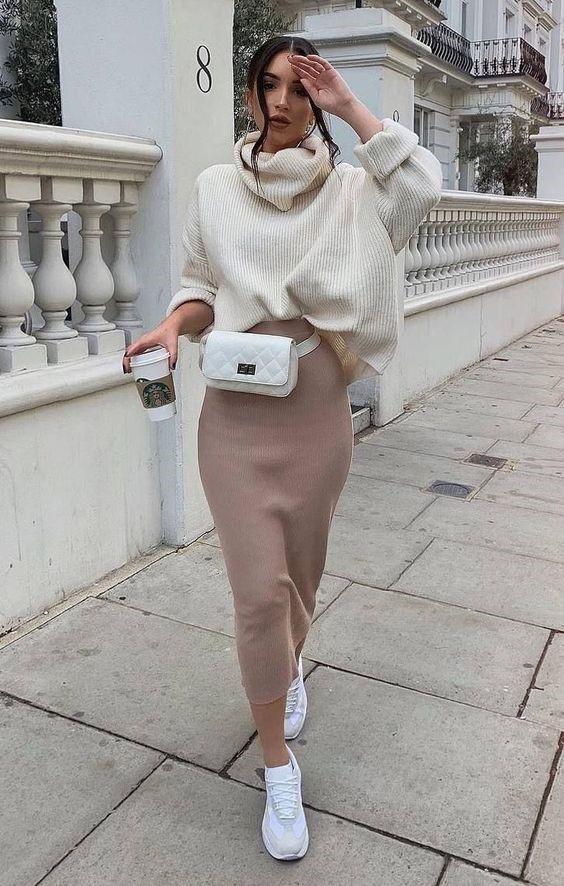 Девушка в трикотажной бежевой юбке, белый свитер оверсайз и белые кеды