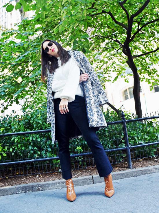 Девушка в укороченных брюках, белый свитер, пальто с принтом и коричневые ботильоны
