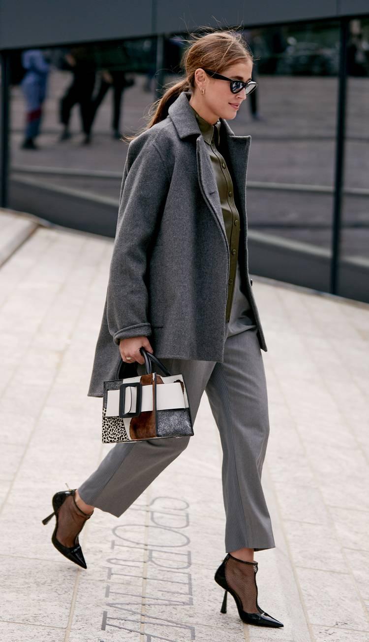 Девушка в укороченных брюках, серое пальто и ботильоны на шпильке