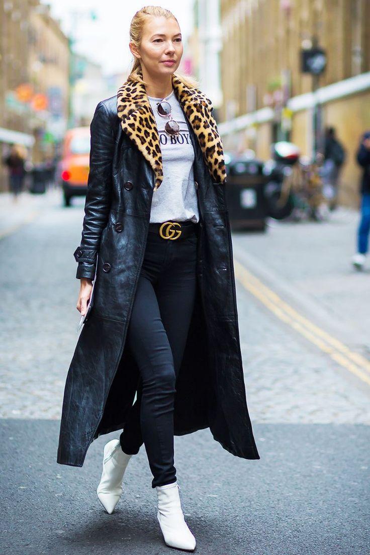 Девушка в узких джинсах, футболка и черное пальто с меховым воротником