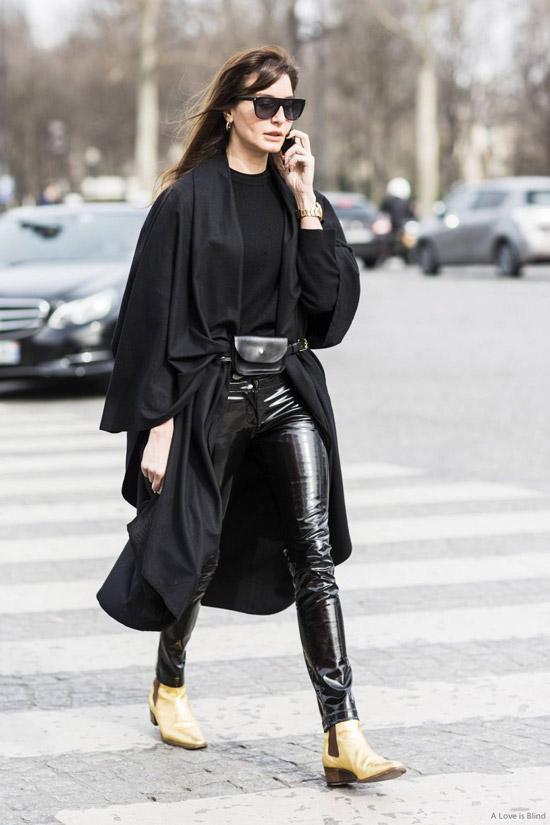 Девушка в виниловых брюках, черный плащ и бежевые ботинки