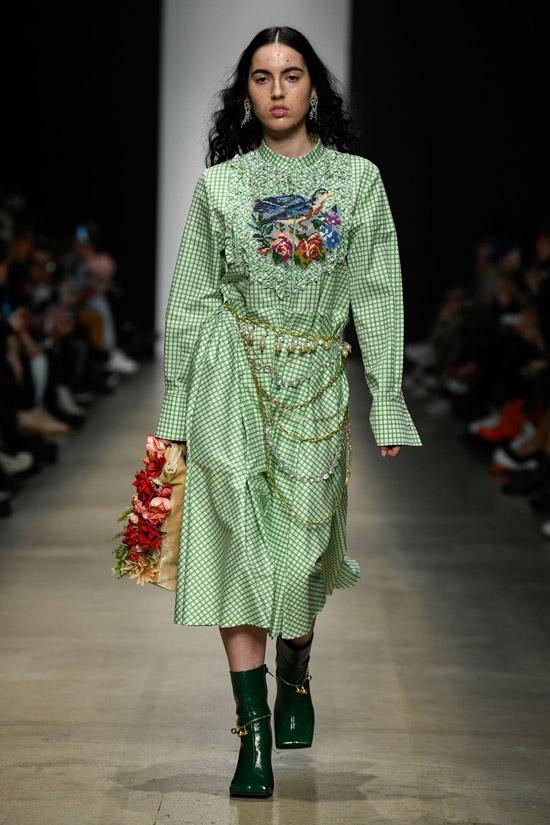 Девушка в зеленом платье миди в клетку с цепями и украшениями и зеленые ботильоны