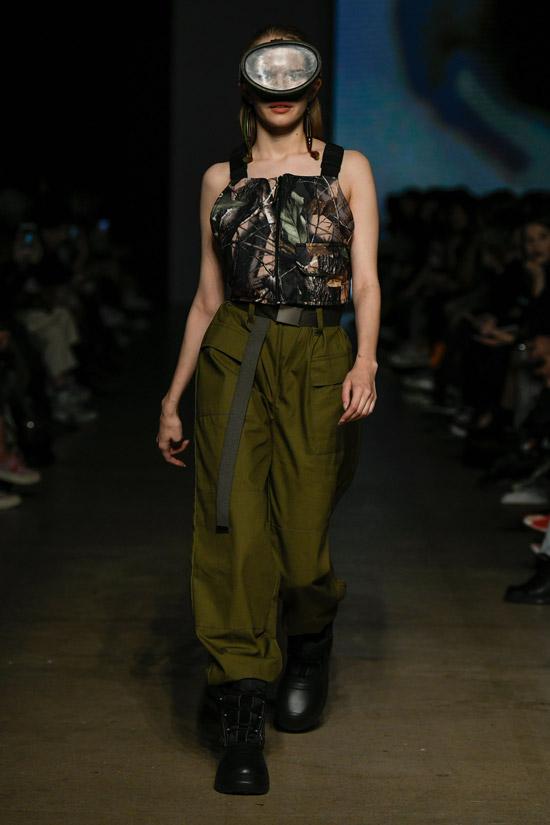 Девушка в зеленых штанах хаки, необычный топ и грубые ботинки