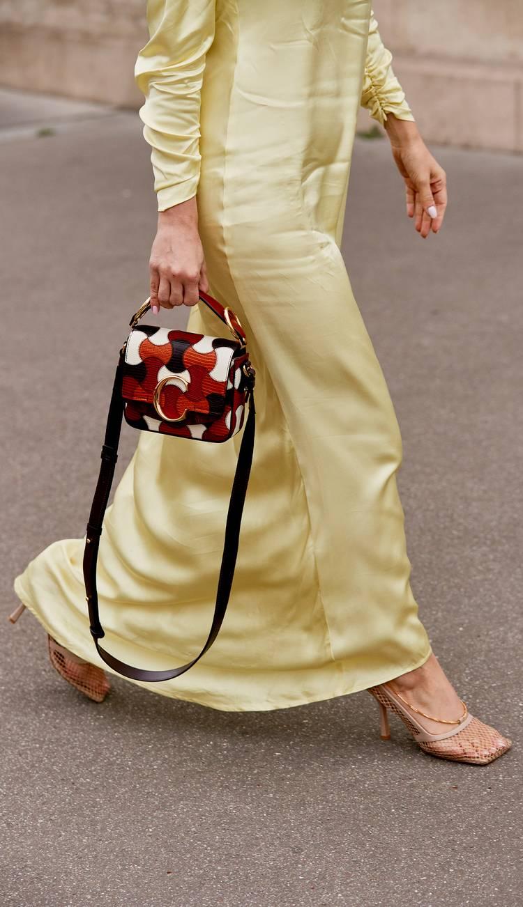 Девушка в желтом атласном платье, бежевые босоножки и сумочка