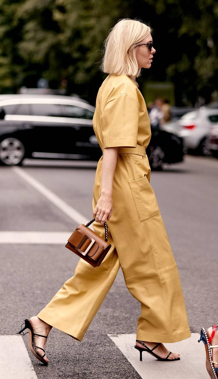 Девушка в желтом комбинезоне, черные босоножки и маленькая сумочка с пряжкой
