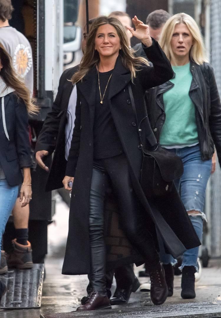 Дженнифер Енистон в черных кожаных лосинах, черное пальто и ботинки на плоской подошве