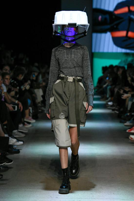 Модель с серых шортах с поясом, серая кофточка и ботинки
