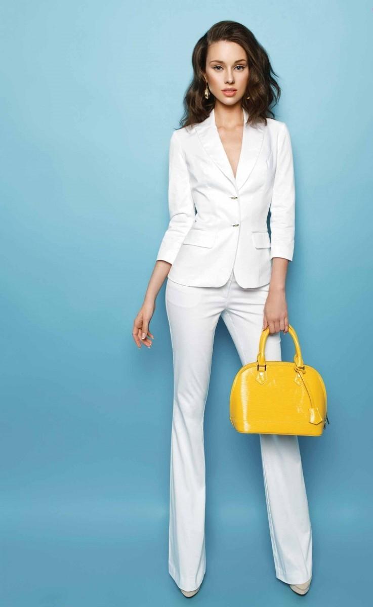 Модель в белом брючном костюме и желтая сумка